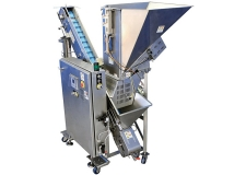 Volumetric filler with batch feeder - Batch Feeder to feed the hopper of the volumetric filling machine.  It can be fed by a post dumper or a conveyor